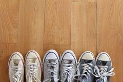 Une ligne de plusieurs paires d'espadrilles de vintage sur un plancher en bois Image stock