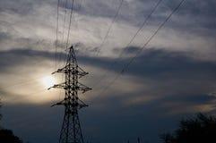 Une ligne des câbles à haute tension contre un ciel gris avec des nuages photographie stock libre de droits