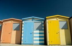 Une ligne des huttes colorées de plage Photographie stock libre de droits