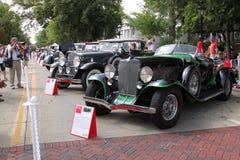 Une ligne des voitures incroyables avalent la rue Images stock