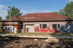 Une ligne ferroviaire et derrière elle un immeuble de brique peint avec le graffiti image stock