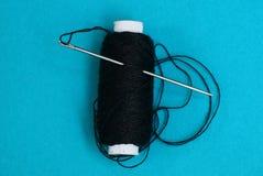 Une longue aiguille avec un fil dans une bobine avec le noir filète sur un fond bleu Photographie stock libre de droits