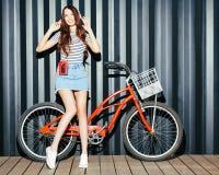 Une longue fille à jambes renversante, une femme asiatique dans un équipement d'été, une jupe de denim, avec un lecteur de casset Photos libres de droits