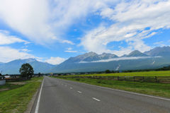 Une longue route à un bel endroit fabuleux parmi les montagnes des champs et des prés Images stock