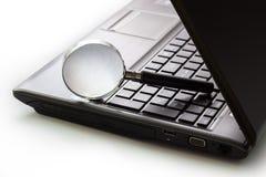Une loupe sur l'ordinateur portable photographie stock libre de droits