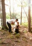 Une lueur douce dans les bois tandis qu'un baiser de couples avec des animaux familiers Photo stock
