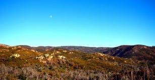 Une lune calme au-dessus des montagnes images stock