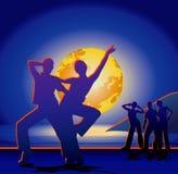 Une lune plus grande au-dessus de la mer et des silhouettes de jeunes hommes sur la côte Photographie stock