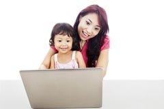 Une mère accompagnent son enfant pour utiliser l'Internet Images libres de droits