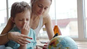 Une mère attirante d'appartenance ethnique caucasienne emploie un globe pour montrer à son jeune fils les pays du monde banque de vidéos