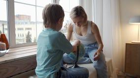 Une mère attirante d'appartenance ethnique caucasienne emploie un globe pour montrer à son jeune fils les pays du monde clips vidéos