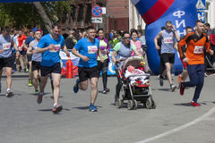Une mère avec un bébé dans une voiture d'enfant court le demi marathon Riazan Kremlin consacré à l'année de l'écologie en Russie Image stock