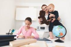 Une mère de deux enfants se tient dans la cuisine Image libre de droits