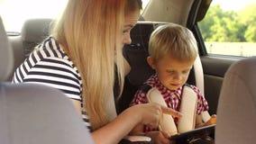 Une mère de soin s'assied à côté de l'enfant dans la voiture, ils jouent le comprimé banque de vidéos