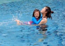 Une mère enseignant sa fille à nager image libre de droits