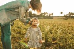 Une mère essuyant la bouche d'un enfant photo stock