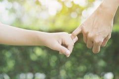 Une mère et son enfant accrochant leurs doigts Images libres de droits