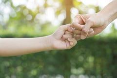 Une mère et son enfant accrochant leurs doigts pour faire une promesse Image stock