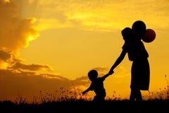 Une mère et un fils jouant dehors à la silhouette de coucher du soleil Photo stock