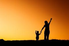 Une mère et un fils jouant dehors à la silhouette de coucher du soleil Photographie stock libre de droits