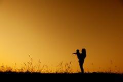 Une mère et un fils jouant dehors à la silhouette de coucher du soleil Photo libre de droits