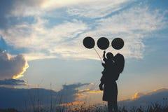 Une mère et un fils jouant dehors à la silhouette de coucher du soleil Photographie stock