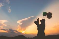 Une mère et un fils jouant dehors à la silhouette de coucher du soleil Images stock