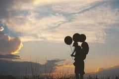 Une mère et un fils jouant dehors à la silhouette de coucher du soleil Image stock