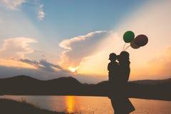 Une mère et un fils jouant dehors à la silhouette de coucher du soleil Images libres de droits