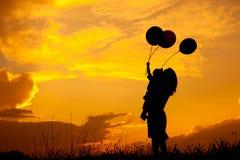 Une mère et un fils jouant dehors à la silhouette de coucher du soleil Photos libres de droits