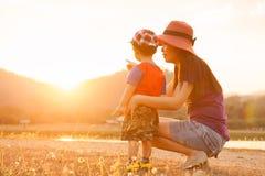 Une mère et un fils jouant dehors au coucher du soleil avec amour Photos libres de droits