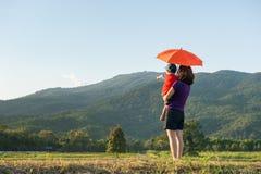 Une mère et un fils tenant le parapluie et jouant dehors au coucher du soleil Image libre de droits