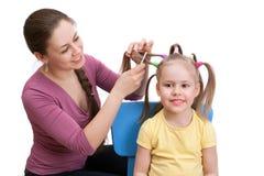Une mère fait à sa petite fille une belle coiffure Image stock