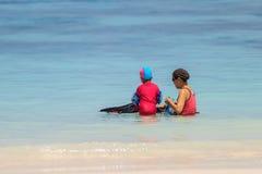 Une mère heureuse avec son enfant avec l'équipement naviguant au schnorchel Images stock