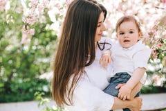 Une mère heureuse avec un bébé dans des ses bras dans les regards blancs de vêtements dans ses yeux sur le fond des fleurs de cer photographie stock
