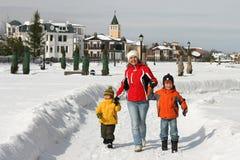 Une mère et deux enfants marchent sur la voie de neige Photographie stock