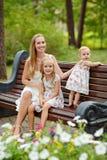 Une mère mince et une séance blonde de deux filles sur un banc dedans Photos libres de droits