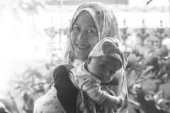 Une mère musulmane tenant sa fille de bébé photos stock