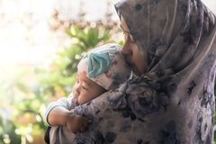 Une mère musulmane tenant sa fille de bébé photo libre de droits
