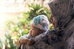 Une mère musulmane tenant sa fille de bébé photo stock