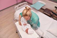 Une mère regarde son bébé nouveau-né dans l'hôpital photos stock