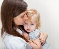 Une mère retient une fille malade. images stock