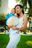 Une mère tient sa petite fille dans l'aodai traditionnel de clothers du Vietnam dans des ses bras sur la plage près des paumes Images stock