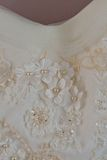 Une macro photo d'une robe de mariage blanche détaillée avec les fleurs blanches et faux les diamants tricotés à la robe Photos libres de droits