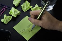 """Une main écrivant sur une note collante verte l'expression """"je suis triste """"Une photo au sujet de dépression, de tristesse et de  image libre de droits"""