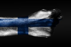 Une main avec un drapeau peint de la Finlande montre une figue, un signe d'agression, le d?saccord, un conflit sur un fond fonc illustration stock