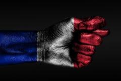 Une main avec un drapeau peint de la France montre une figue, un signe d'agression, le désaccord, un conflit sur un fond foncé illustration de vecteur