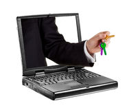 Une main collant par un ordinateur portatif donnant une clé. Photos libres de droits