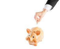 Une main d'homme d'affaires insérant une pièce de monnaie dans une tirelire d'isolement, le concept pour des affaires et épargnent Photo stock