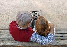 Une main d'homme supérieur et de femme utilisant un téléphone portable d'écran tactile Images stock